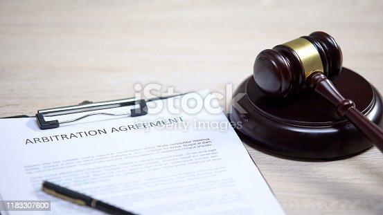 istock Arbitration agreement document on table, gavel lying on sound block, dispute 1183307600