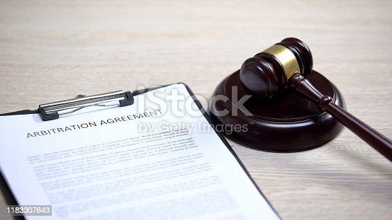 istock Arbitration agreement table, gavel lying on sound block, conflict settlement 1183307643