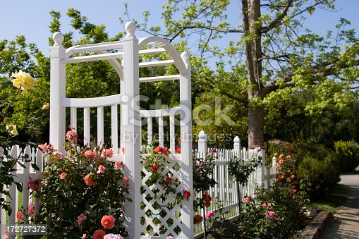 A picket fence and an arbor in a well-tended front yard.
