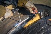 Welder in protective uniform and mask welding metal pipe