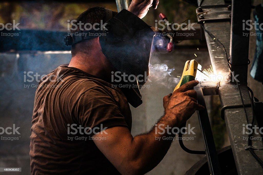 Welder at work, using arc welding for welding a metal construction...