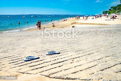 The Bay of Arcachon beach in Western France in the Arcachon Basin. This shows the beach and Atlantic sea with tourists on the beach in the afternoon sun and a pair of flip flops on the slipway in the foreground.