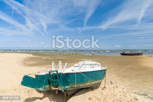 Arcachon Bay, France - August 19, 2017: boats at low tide on the beach of Claouey, near the Cap Ferret, one of the 23 oyster villages of the Arcachon Bay.