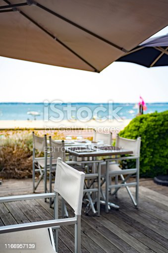 Arcachon Bay in Western France below the Arcachon Basin. This shows the tables and chairs outside a bar and restaurant on the beach in the late afternoon sun.
