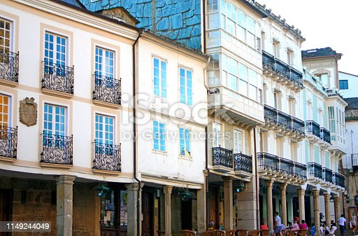 Arcade, pedestrian street view in old town Mondoñedo. People in sidewalk cafes,town square, row of residential building facades and staircase in old town Mondoñedo, Lugo province, A Mariña, Galicia, Spain.