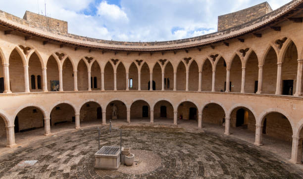 Arcades of the inner courtyard of Bellver castle with a water well in the middle in Mallorca, Spain. Historic Building stock photo