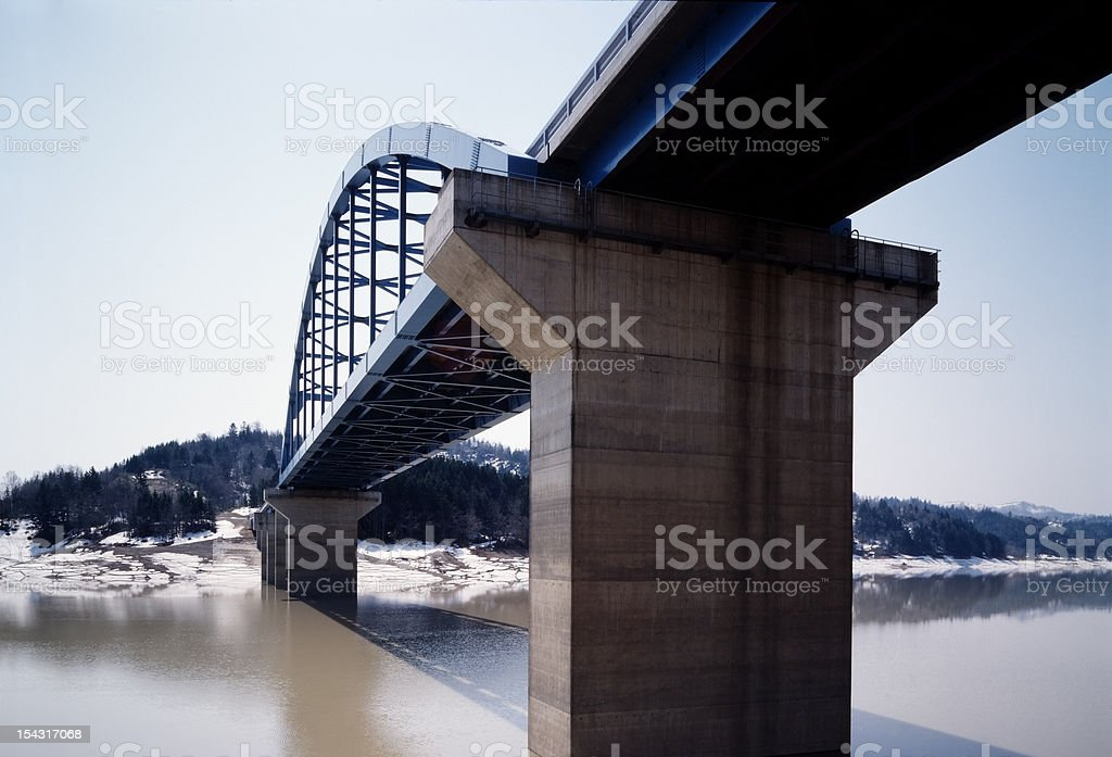 Arch bridge is built over the dam stock photo