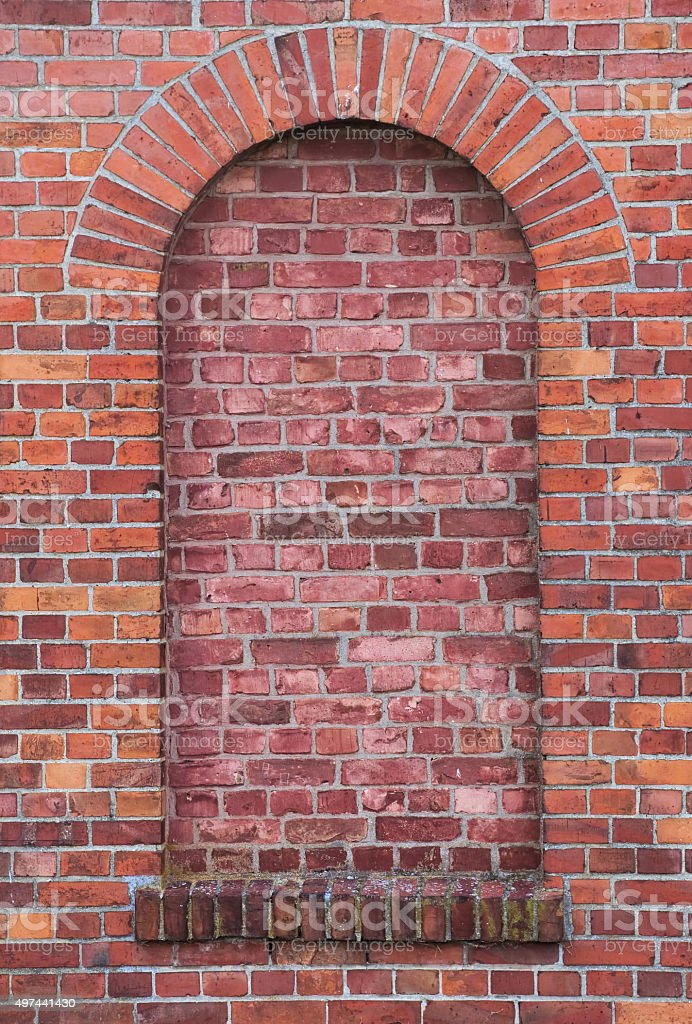 Arch in a wall made from red bricks stock photo