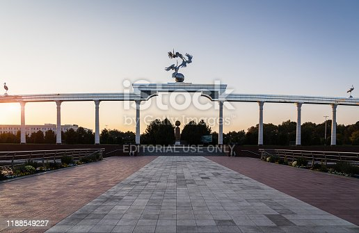 Tashkent, Uzbekistan - October 24th, 2019: View from Independence Square to sunset twilight over the Arch of Independence. Monument to the Independence of Uzbekistan - Mustaqillik Maydoni at Independence Square in the background. Independence Square, Tashkent, Uzbekistan, Central Asia.