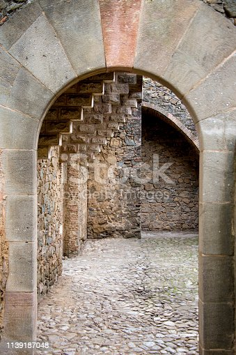 Architectural arch of natural stone, leading to the courtyard with stone paving, built by the great architect.