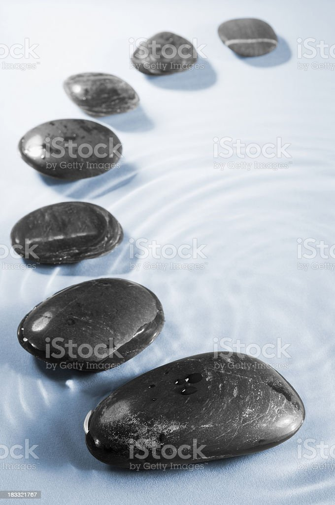 Arch of pebbles in water emanating ripples stock photo