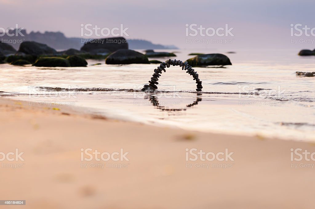Arch of pebbles on the beach stock photo