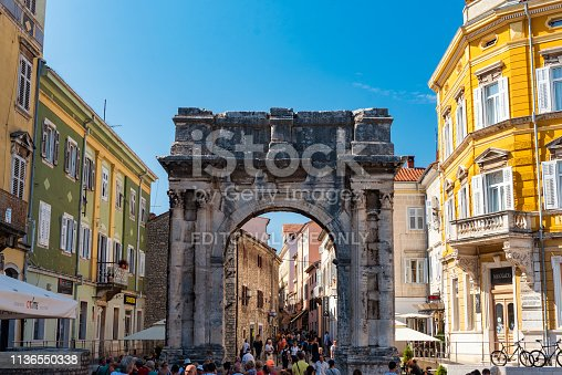 Pula, Croatia - September 18, 2018: Arch of the Sergii is an Ancient Roman triumphal arch located in Pula, Croatia. The arch commemorates three brothers of the Sergii family, specifically Lucius Sergius Lepidus, a tribune serving in the twenty-ninth legion that participated in the Battle of Actium and disbanded in 27 BC.