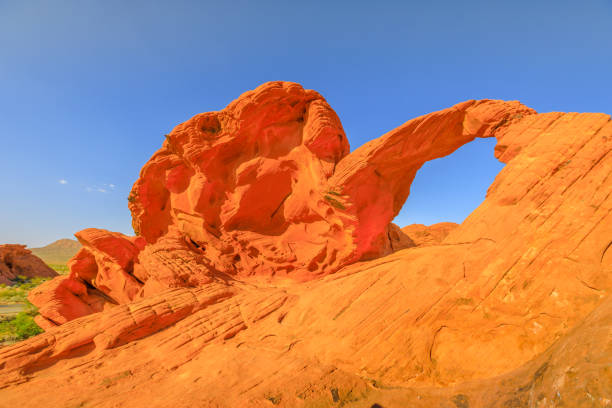 Arch Rock Valley of Fire The iconic Arch Rock a natural arch along Valley of Fire scenic loop, Nevada's oldest state park famous for red sandstone formations formed from great shifting sand dunes during the age of dinosaurs. mojave desert stock pictures, royalty-free photos & images