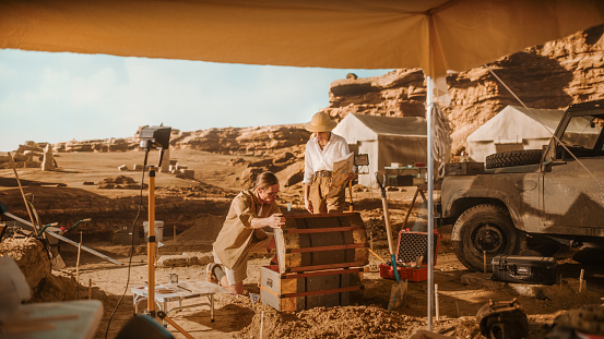 Archaeological Digging Site: Two Great Adventurers on Treasure Hunt Talk and work with Opened Chest with Unspeakable Treasures. Ancient Civilization Hidden Gold Found