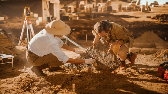Archaeological Digging Site: Two Great Archeologists Work on Excavation Site, Carefully Cleaning, Lifting Newly Discovered Ancient Civilization Cultural Artifact, Historic Clay Tablet, Fossil Remains