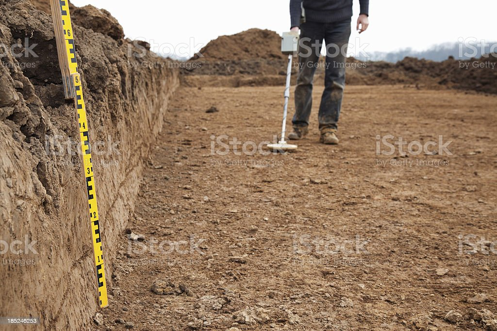 Archaeologist at excavation site, using metal detector stock photo