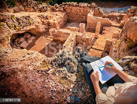 archaeologist taking notes at roman ruins