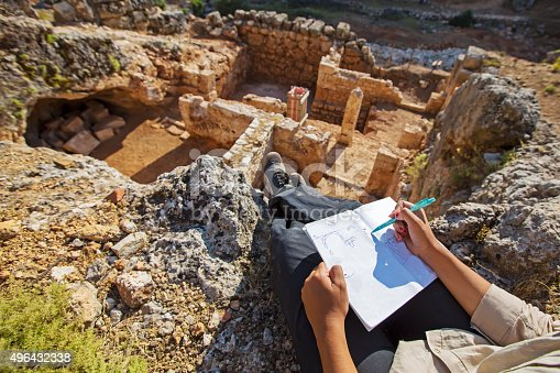 Archeaologist working and notes on site
