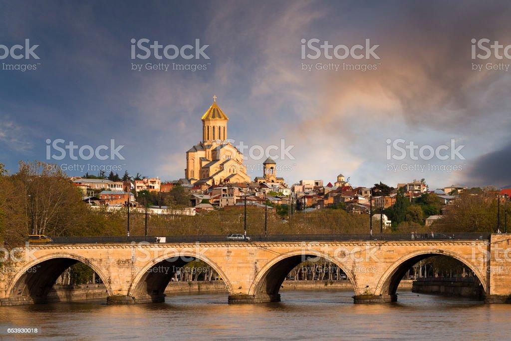 Arched bridge known as Saarbrucken Bridge on the River Mtkvari or Kura, with Sameba Cathedral in the background, Tbilisi, Georgia stock photo