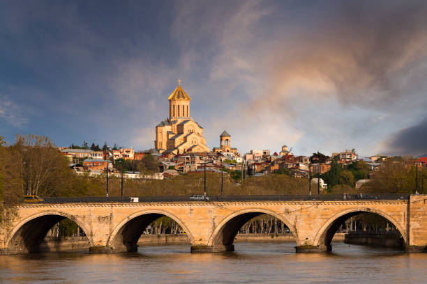 Arched bridge known as Saarbrucken Bridge on the River Mtkvari or Kura, with Sameba Cathedral in the background, Tbilisi, Georgia stock photo