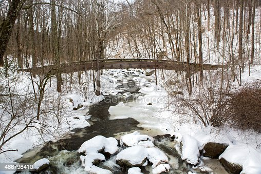 An arched wooden bridge goes over a mountain River at Crabtree Falls State Park in Virginia. Taken after a snow storm, there is ice and snow in the forrest around the river and on the stones in the creek. The River has frozen over except for the fastest flowing parts of the water. The trees are bare and makes for a scenic, remote winter nature landscape. - A great shot taken in the outdoors.