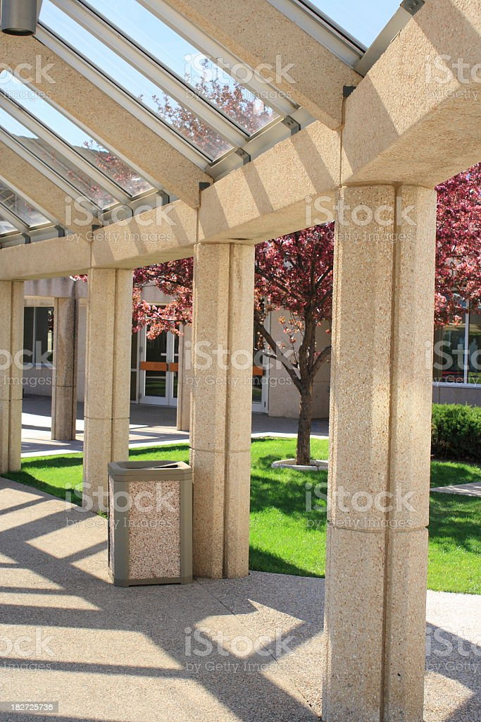 arched concrete covered walkway in spring - tree blooms stock photo