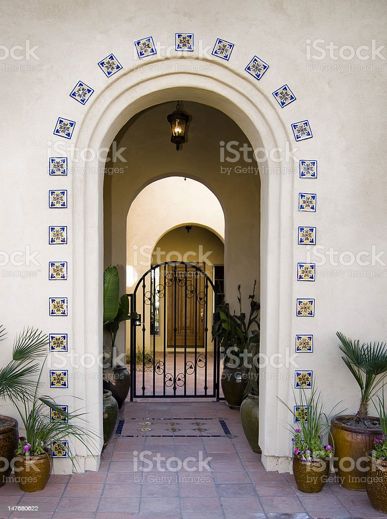 Arched doorway entrance with gate and potted tropical plants royalty-free stock photo