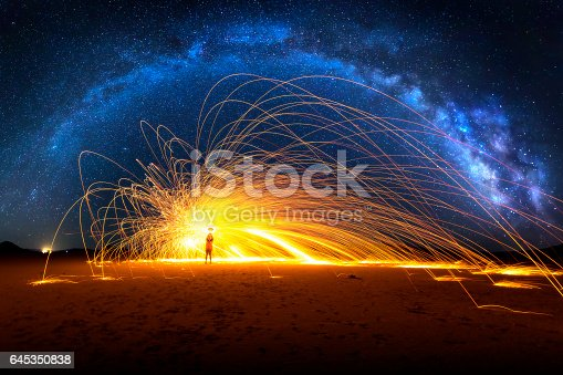 istock Arched Milky Way and Fiery Sparks on desert lake bed 645350838