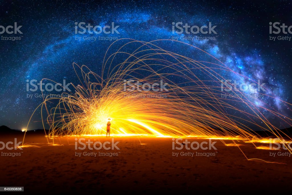 Arched Milky Way and Fiery Sparks on desert lake bed stock photo