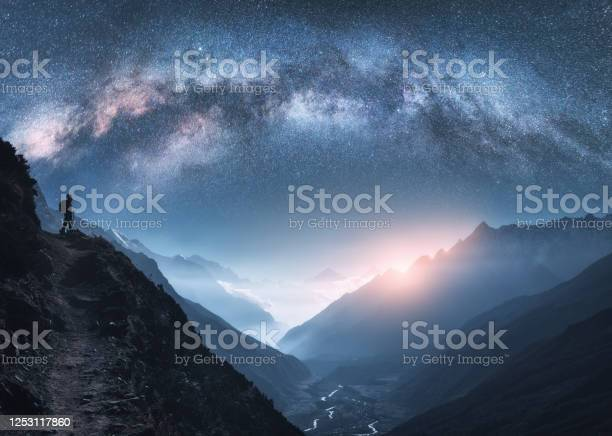 Photo of Arched Milky Way, woman and mountains at night. Silhouette of standing girl on the mountain peak, mountains in low clouds and starry sky in Nepal. Space landscape with bright milky way arch. Travel