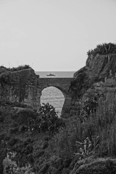 Arched stone bridge between coastal headlands. stock photo