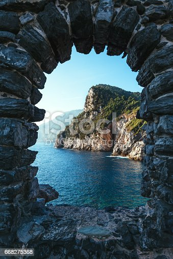 istock Arched stone window overlooking scenic landscape of ligurian sea and mountains in Italy. 668275368