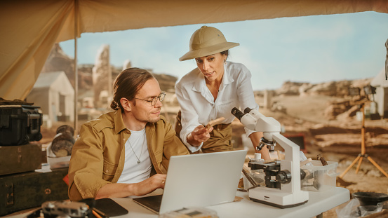 Archeological Digging Site: Two Great Archeologists Talk about Ancient Civilization, Cultural Artifacts, Fossil Remains, Use Laptop for Analysis. Diverse Team of Historians Research Excavation Site