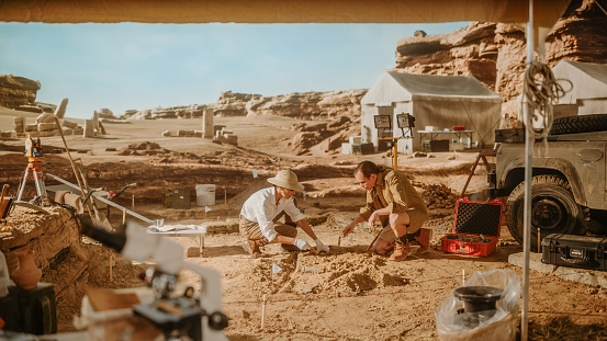 Archeological Digging Site: Two Great Archeologists Work on Excavation Site, Carefully Cleaning with Brushes and Tools Newly Discovered Ancient Civilization Cultural Artifacts, Fossil Remains