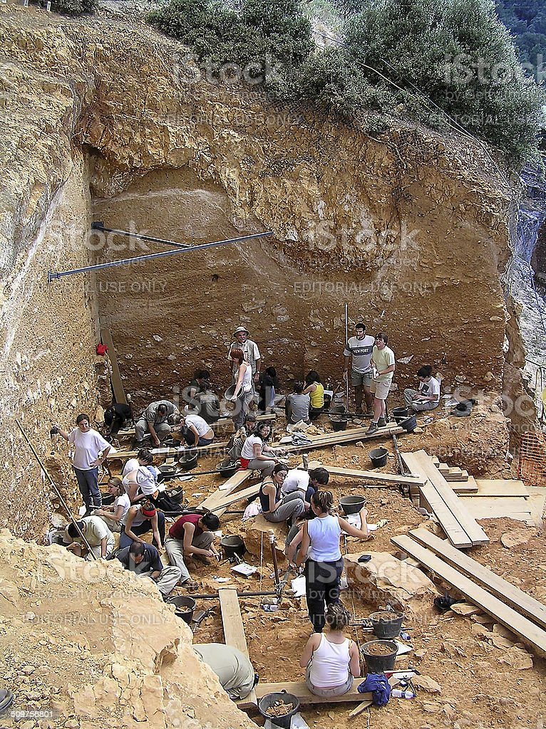 Archeological Site of Atapuerca Atapuerca, Spain - August 5, 2005: Some researchers work in Atapuerca site, where fossils and stone tools of the earliest known humans in West Europe have been found, Adult Stock Photo