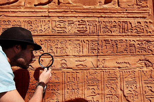 Archeologist Archeologist reading hieroglyphics with magnifying glass archaeology stock pictures, royalty-free photos & images