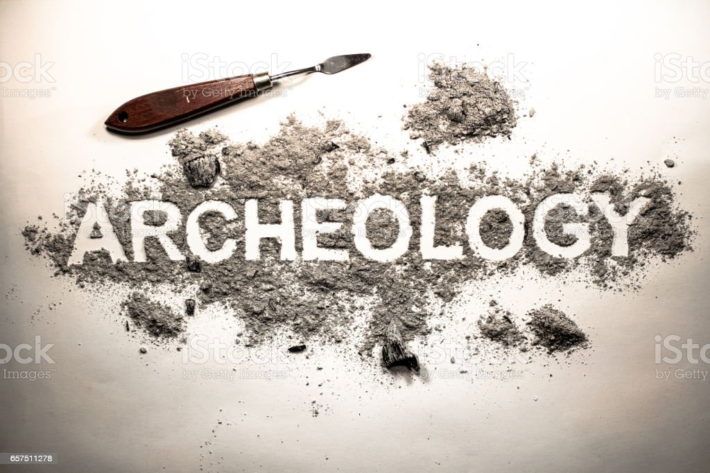 Archeology word written in letters on a pile of grey ash, dirt, soil, ground stock photo
