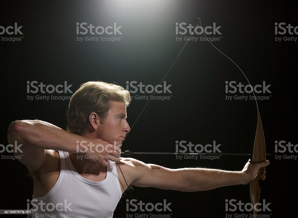 Archer aiming bow and arrow, on black background 免版稅 stock photo
