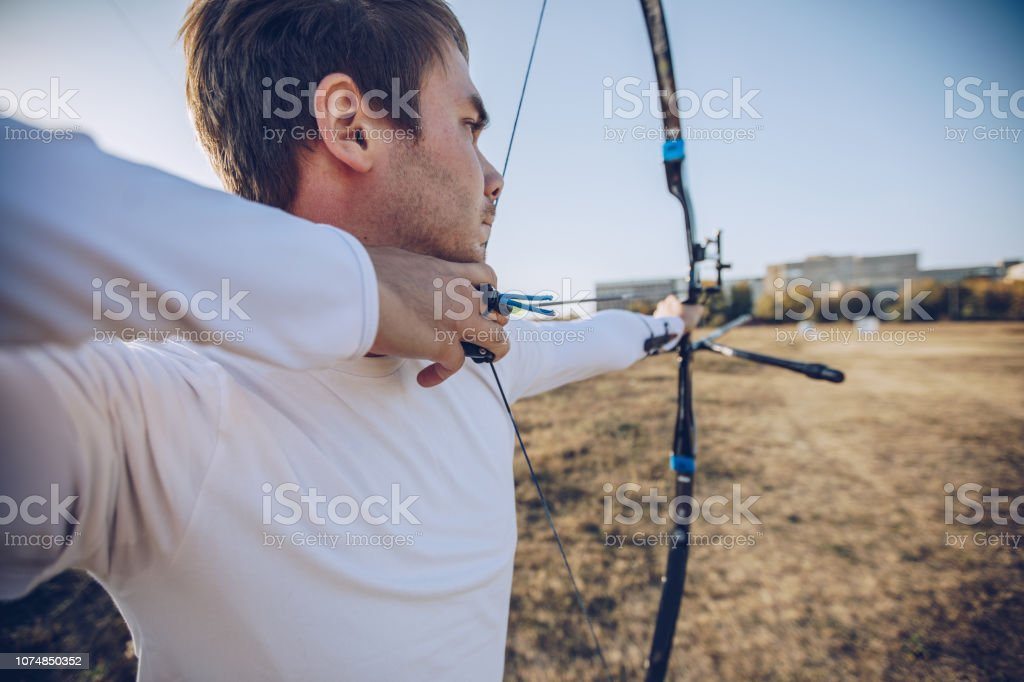One man, young archer with bow and arrow training alone outdoors.