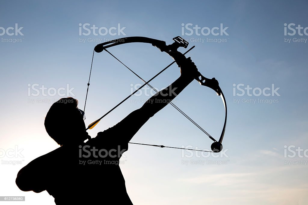 Archer drawing his compound bow silhouette stock photo