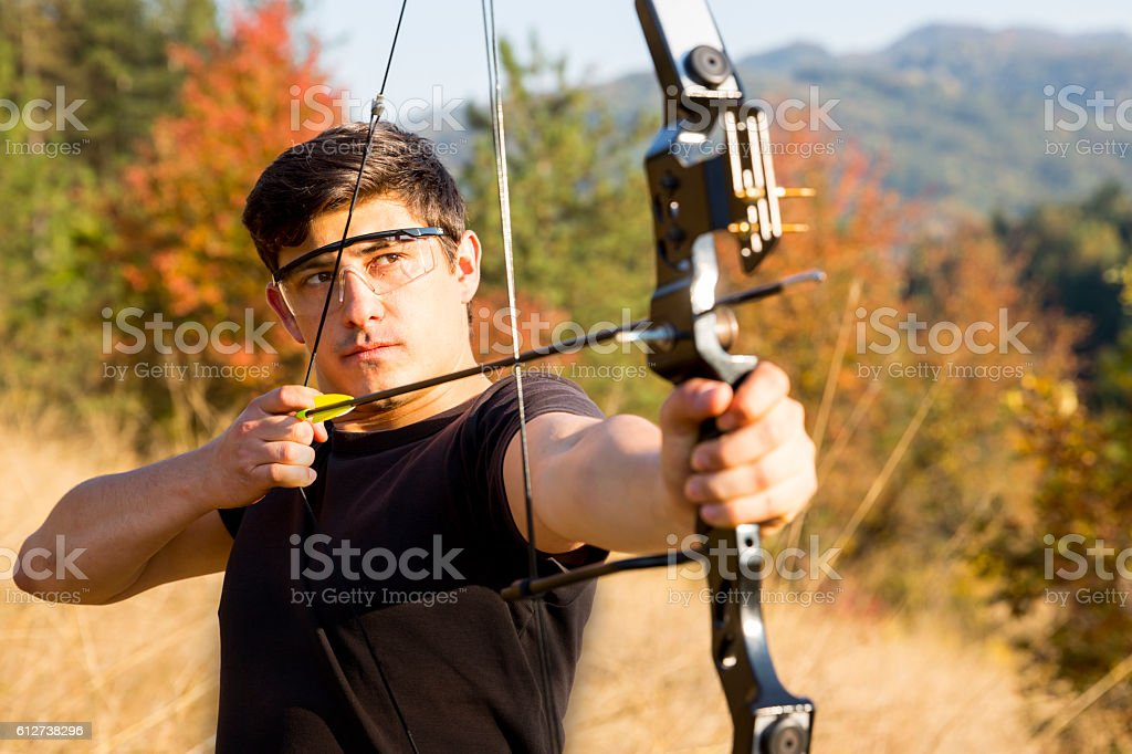 Archer drawing his compound bow trees stock photo