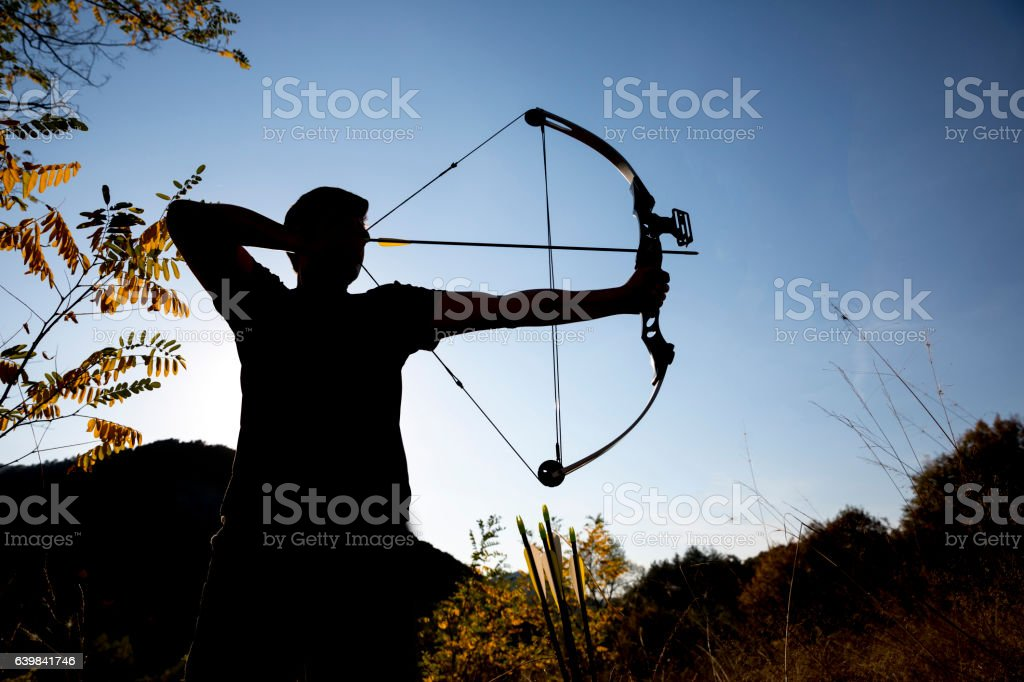 Archer draws his compound bow silhouette stock photo