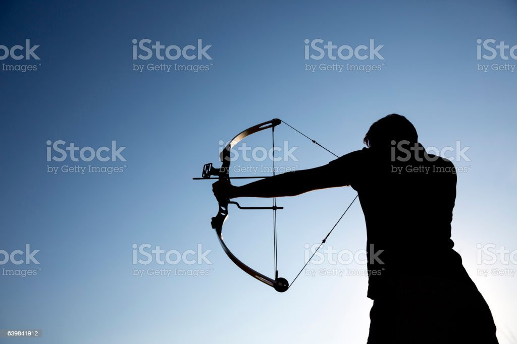 Archer draws his compound bow silhouette stock photo