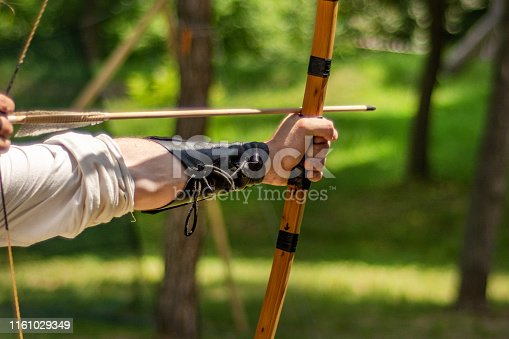 istock Archer hand holds his bow with an arrow and aiming at the target 1161029349