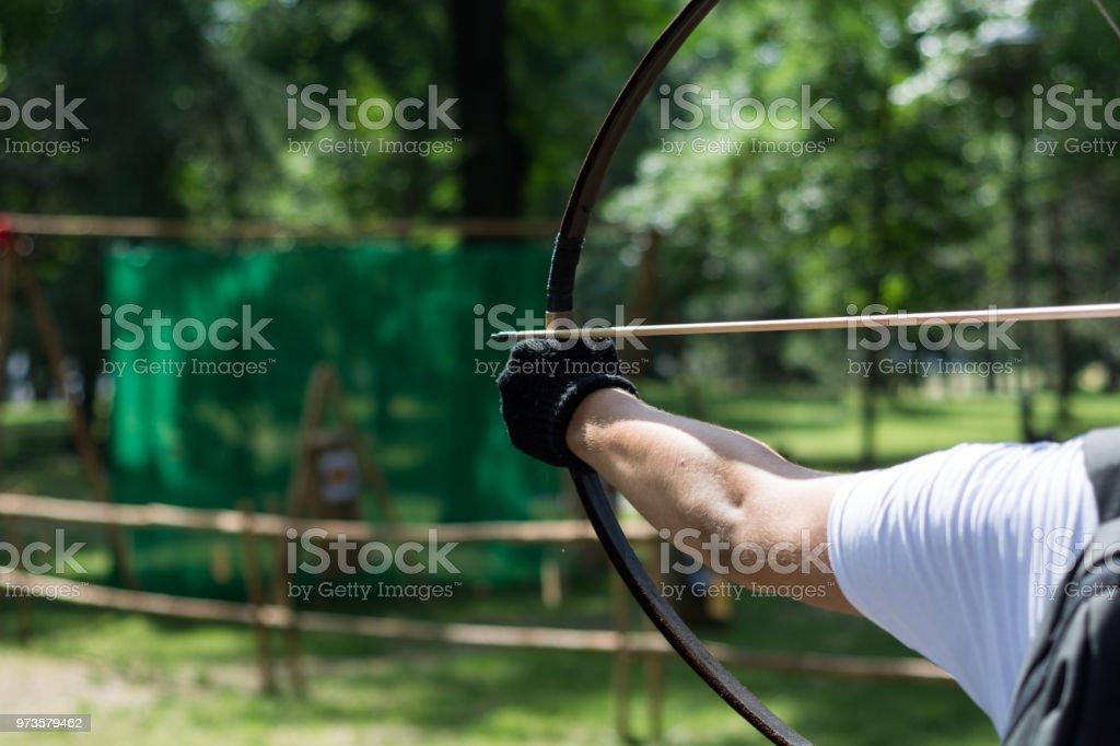 Las manos del arquero con el arco de madera disparan flecha. Torneo de tiro con arco en bosque - foto de stock