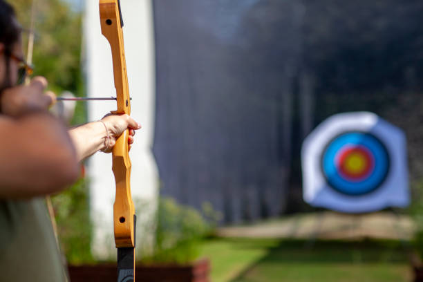 Archer holding wooden bow and aiming at unfocused target board Archer holding wooden bow and aiming at unfocused target board image focus technique stock pictures, royalty-free photos & images