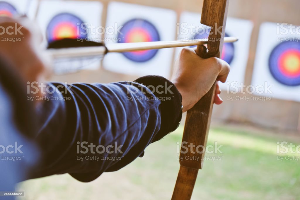 Archer holds his bow aiming at a target stock photo