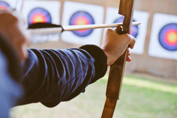 archer détient son nœud visant à la cible - tir à l'arc photos et images de collection