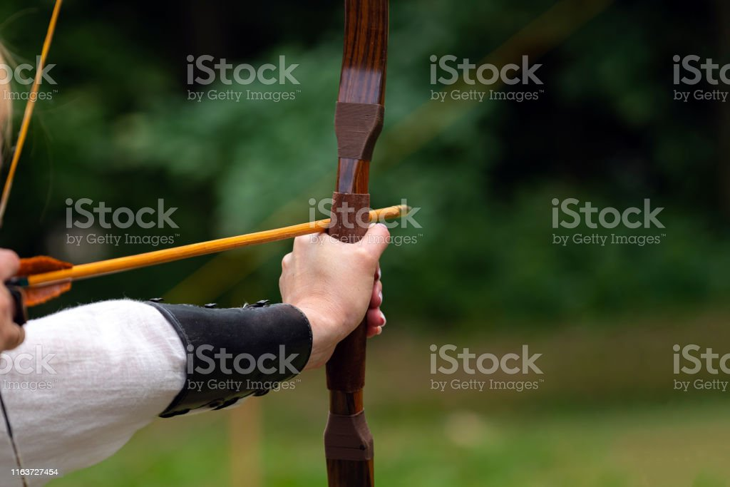 Archer holds his bow aiming at the target. Archery competition,...